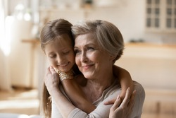 Head shot close up happy mature woman with adorable little girl hugging, enjoying tender moment, caring grandmother piggy backing preschool granddaughter, two generations warm family relationship