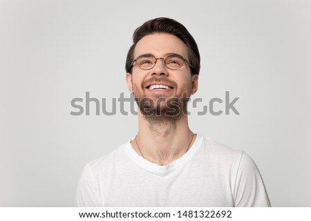 Head shot close up happy millennial handsome bearded man in eyeglasses looking up, smiling stylish young guy in eyewear dreaming, positive thinking, isolated on grey studio background portrait.