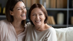 Head shot close up happy young woman hugging mature brunette mother, feeling excited about positive news at home. Smiling two female generation family dreaming of future together, resting on sofa.