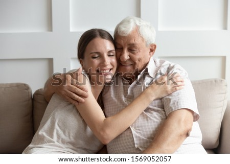Head shot close up portrait caring adult young woman cuddling happy older hoary father. Smiling loving two generations family enjoying sweet tender moment, sitting together on couch at home.