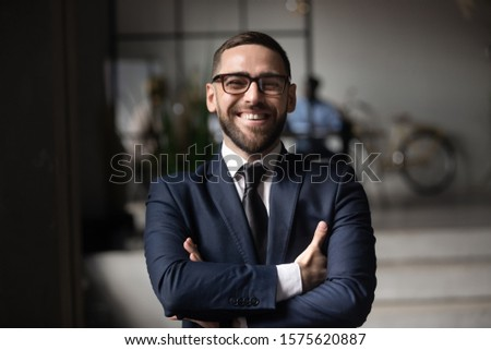 Head shot close up portrait happy businessman entrepreneur investor in eyeglasses standing with folded hands. Smiling cheerful confident company owner director manager worker lawyer looking at camera.