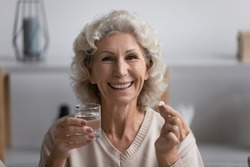 Head shot close up portrait happy elderly senior woman looking at camera, holding glass of fresh water and pill. Smiling mature grandmother taking vitamins, enjoying daily healthcare habit at home