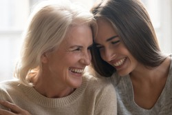 Head shot close up portrait happy smiling mature mother and grown up adult daughter bonding, touching foreheads, laughing, having fun together, enjoying free time together, two generations relations.