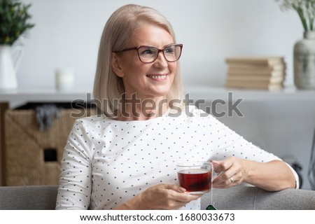 Photo of Head shot close up portrait happy stylish older lady in eyewear relaxing alone with cup of tea on comfortable sofa at home. Smiling middle aged woman enjoying weekend leisure free time, dreaming.