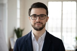 Head shot close up portrait of young confident businessman in eyeglasses. Smart professional bearded coach trainer speaker ceo executive in formal wear posing for photo alone, looking at camera.