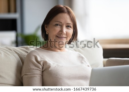Head shot close up portrait smiling middle aged woman sitting on couch with laptop, looking at camera. Happy older senior grandmother using computer alone at home, retired people technology concept.