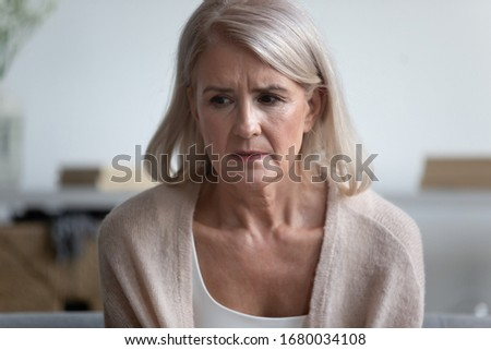 Head shot close up portrait unhappy older female retiree sitting alone, trying remember important event or information. Frustrated worrying middle aged sad woman having problem with memory or health.