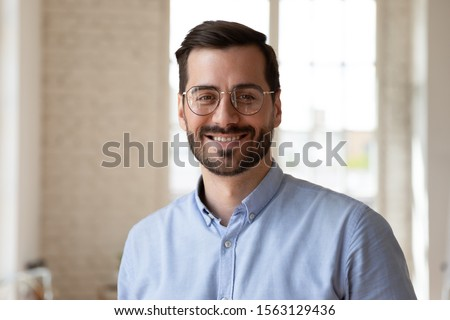 Head shot close up portrait young smiling businessman in eyeglasses posing at office for photo. Confident happy male professional speaker blogger looking at camera, recording educational video.