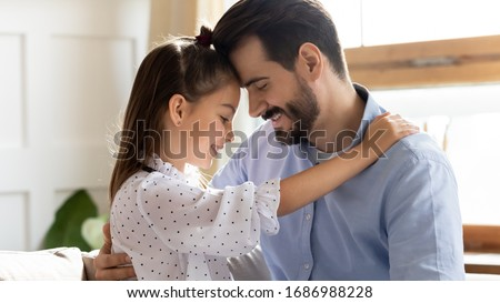 Head shot close up side view affectionate little child daughter touching foreheads with smiling bearded father. Happy small kid girl enjoying sweet moment with dad in living room, trustful relations.
