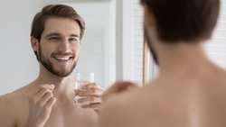 Head shot close up smiling young man looking in mirror, holding glass of water and pills, taking morning medicine or healthcare vitamins, improving immunity every day, feeling healthy and energetic.