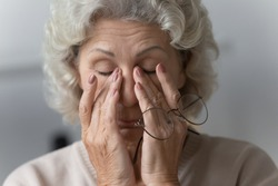 Head shot close up tired middle aged mature woman rubbing nose bridge after taking off eyewear. Frustrated stressed senior older grandmother suffering from blurred eyesight, eyes strain pain ache.