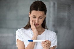 Head shot close up unhappy frustrated young woman looking at plastic test, worrying about pregnancy confirmation or denial. Anxious stressed brunette lady waiting for results, maternity concept.
