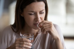 Head shot close up unhealthy young woman taking painkiller, suffering from strong headache. Unhappy frustrated lady holding glass of pure water and antidepressant medicine, healthcare concept.