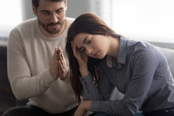 Head shot close up upset abused offended woman sitting on sofa, ignoring her apologizing husband. Young man feeling sorry, asking forgiveness to depressed wife. Family relationship problems concept.