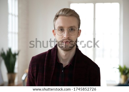 Head shot close up young blonde employee worker in glasses looking at camera. Portrait of millennial colleague coworker designer businessman entrepreneur posing for photo in light workplace.