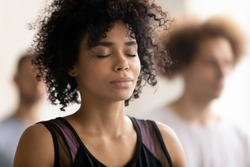 Head shot close up young peaceful attractive curly hair african american woman breathing fresh air, enjoying deep meditation with closed eyes, relaxing after yoga class workout in sport club.