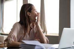 Head shot distracted from work study young woman yawning, having lack of energy during workday at home or office. Tired businesswoman feeling bored, looking at window, chronic fatigue concept.