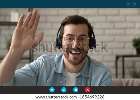 Head shot emotional happy 30s man in eyeglasses and wireless headphones, looking at camera, making hello gesture, greeting friends starting online video call, computer application monitor view.