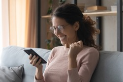Head shot emotional young woman in glasses looking at mobile screen, amazed by good news notification. Overjoyed pretty lady celebrating online lottery win, reading success victory message at home.
