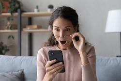 Head shot emotional young woman looking at smartphone screen with opened mouth, feeling surprised with received offer. Amazed millennial lady getting sms with unbelievable news. shocked by sale prices