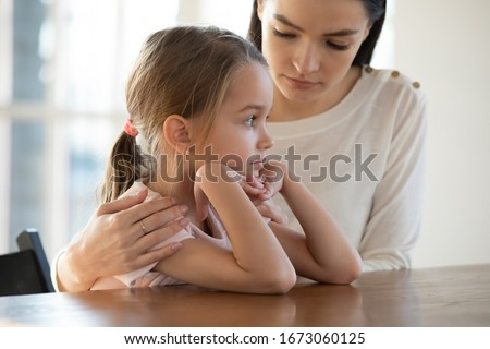 Head shot empathic worried young mother embracing upset little offended daughter, reconciling after quarrel. Compassionate loving mother helping unhappy small child girl overcoming problems at home. Stock photo ©