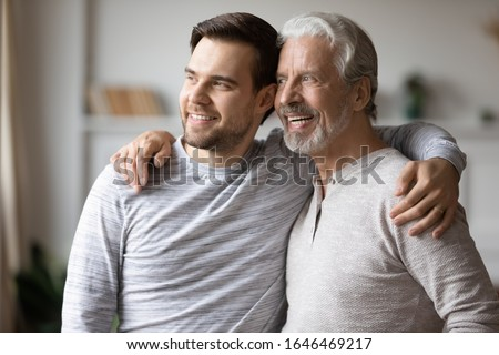 Head shot excited grown up son embracing shoulders of happy middle aged father, looking at window. Positive two male generations family supporting each other, visualizing planning future together.