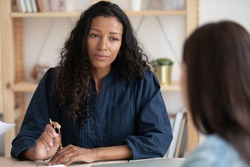 Head shot focused african american female leader boss supervisor listening to employee at meeting. Concentrated biracial hr manager holding job interview. Mixed race businesswoman consulting client.