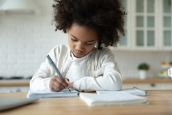 Head shot focused small 7 years old african american child girl sitting at table, handwriting school tasks alone at home, serious busy little mixed race female pupil studying remotely, education