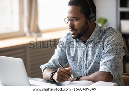 Head shot focused young african american man in glasses wearing wireless headphones, looking at laptop screen, watching educational lecture seminar webinar online, studying remotely, writing notes.
