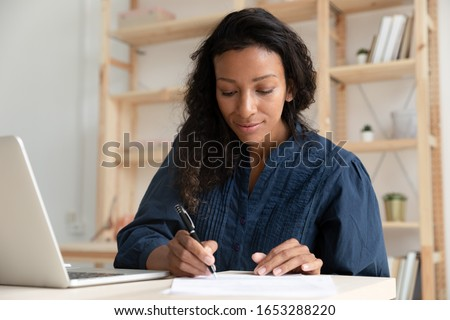 Head shot focused young mixed race female manager company worker sitting at desk alone in office, working with financial documents. Concentrated professional writing notes while watching webinar.