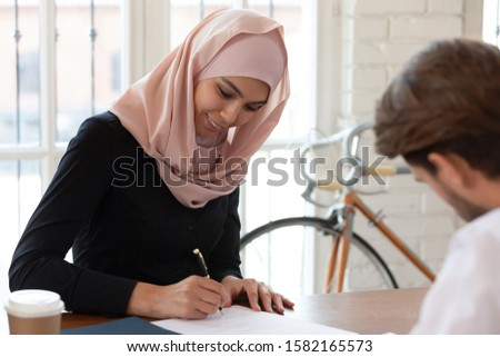 Head shot happy arabic businesswoman satisfied with negotiations results, signing agreement with business partner at office. Smiling female arabian manager putting signature on contract with client.