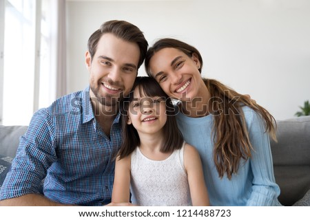 Head shot happy diverse family sitting on couch have video call smiling looking at camera, small daughter spend time on weekend together with parents communicate with friends or relatives via internet
