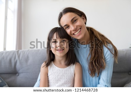 Head shot happy family sitting on couch have video call smiling looking at camera, small daughter spend time on weekend together with young mother communicate with friends or relatives via internet