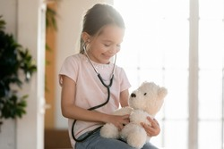 Head shot happy playful little patient wearing stethoscope, pretending to be doctor checking lungs of fluffy toy in clinic or home. Happy small girl playing nurse, holding favorite teddy dog.