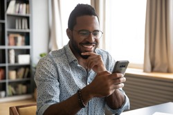 Head shot happy young african american man in eyeglasses looking in phone screen. Smiling millennial biracial guy reading pleasant good news sms in smartphone, enjoying chatting communicating online.