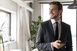 Head shot happy young dreamy ceo manager in formal wear holding mobile phone in hands, thinking of business opportunity alone in office, smiling leader planning workday, feeling excited of good news.
