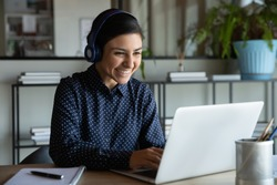 Head shot happy young indian ethnicity female manager wearing wireless headphones, looking at laptop screen, holding pleasant conversation with partners clients online, working remotely at workplace.