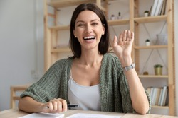 Head shot happy young 30s woman sitting at wooden desk, looking at camera, waving hello. Excited businesswoman teacher lecturer recording educational video, greeting students at online workshop.
