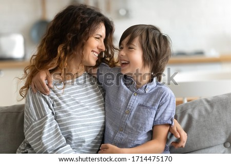 Head shot happy young woman cuddling talking to small kid son, having fun together on couch in studio living room. Smiling child boy communicating with elder sister nanny babysitter, laughing at home.
