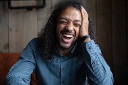 Head shot hilarious long-haired African guy close up portrait, sit indoors laughing over joke feels excited. Video call funny conversation with friend, happy mood enjoy talk with mate in cafe concept