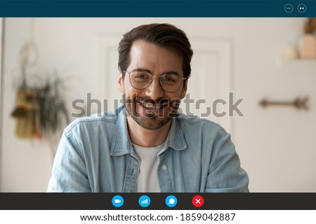 Head shot laptop screen view handsome young 30s man in eyeglasses looking at camera, enjoying pleasant distant online conversation, communicating by video call computer software application indoors.