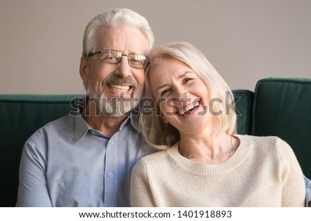 Head shot laughing retirees pretty couple sitting on couch at home, spouses having candid healthy toothy smile, dental treatment check-up services for old people, medical insurance health care concept