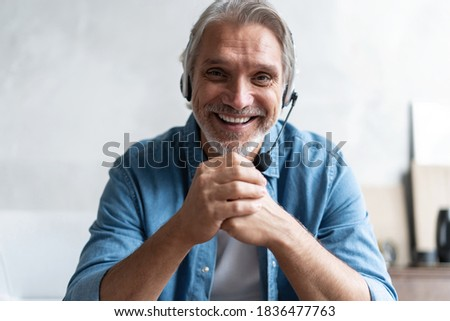 Head shot man sit on sofa in living room makes video call looks at camera, conversation by distant videocall, distance hiring job interview process, tutor and trainee study on-line concept.