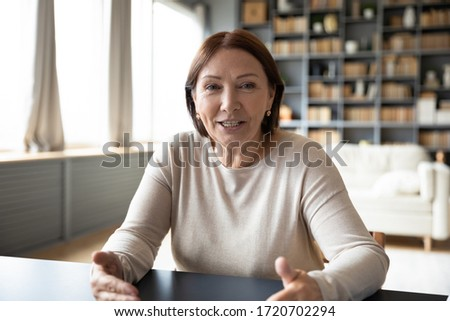 Head shot mature woman looking at camera and talking, grandmother chatting with relative online, making video call, middle aged blogger recording vlog, teacher speaking to webcam, distance lecture