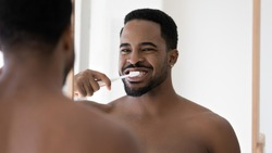 Head shot mirror reflection African American handsome young man with healthy toothy smile cleaning brushing teeth, standing in bathroom, enjoying morning routine, oral hygiene concept