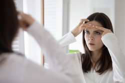 Head shot mirror reflection unhappy annoyed young woman squeeze pimple on forehead, dissatisfied girl wearing white bathrobe checking face, standing in bathroom, skin problem and acne
