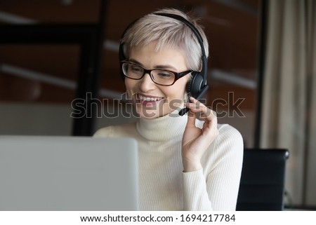 Head shot motivated successful happy 30s female company employee boss leader in eyeglasses wearing wireless headset with mic, looking in computer screen, holding video call negotiations with partners. Сток-фото ©