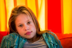 Head shot of a beautiful, 11 years old girl sitting in front of a red and orange curtain