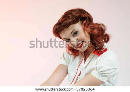 Head shot of a pretty pin-up girl on a soft pink background.