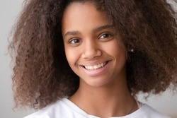 Head shot of african american teen girl looking at camera, black female adolescent teenager with pretty face posing alone, smiling teenage generation z school child with afro hair close up portrait